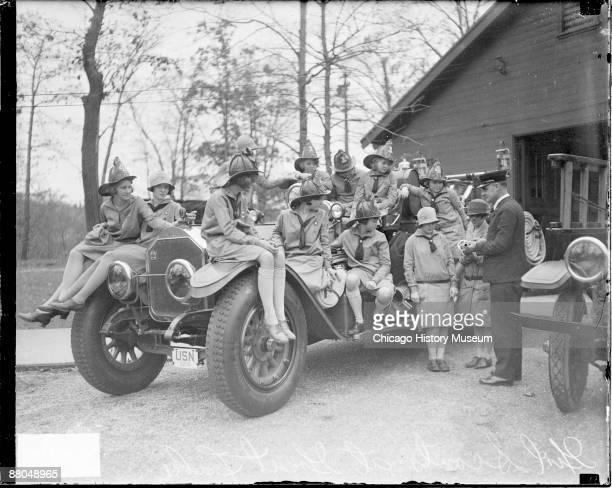 Informal fulllength portrait of a group of Girl Scouts sitting on a large automobile in front of a building in Great Lakes Naval Training Station in...