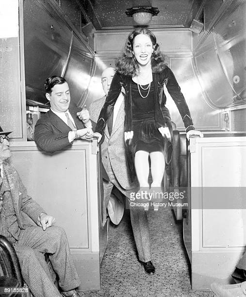 Informal fulllength portrait of actress Lupe Velez bracing her hands on two low counters and holding her feet in the air in a passenger train car...