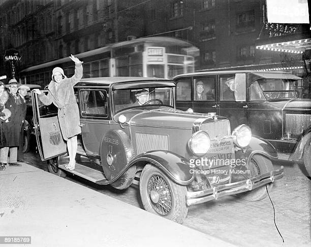 Informal fulllength portrait of actress Lupe Velez waving and standing on the railing of an automobile parked along a curb in Chicago Illinois...