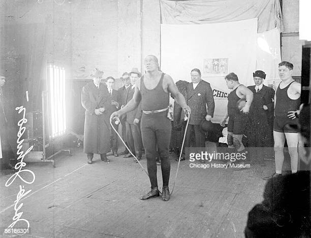 Informal fulllength portrait of African American pugilist Jack Johnson holding a rope by both ends and stepping on the middle of the rope standing in...