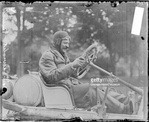 Informal full-length portrait of automobile driver L. Chevrolet sitting in profile in the driver's seat of a Buick automobile parked on a road in...