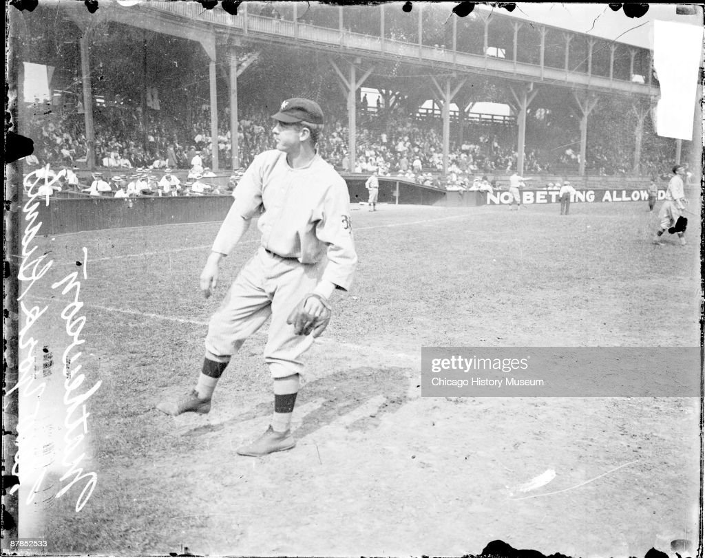 Informal full-length portrait of baseball player Christopher 'Christy' Mathewson of the National League's New York Giants, following through after throwing a baseball, standing in profile on the field at West Side Grounds, in the Near West Side community area of Chicago, Illinois, 1911. Text on grandstand wall in the background reads: No Betting Allowed. From the Chicago Daily News collection.