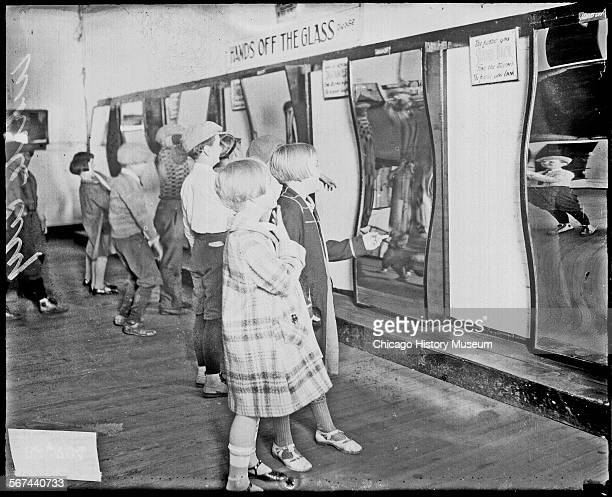 Informal full-length portrait of children standing in front of a display of trick mirrors at the White City amusement park, located at 63rd and South...