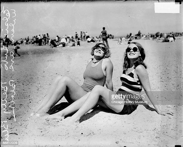 Informal full-length portrait of Elsie Luto and Betty Blee wearing bathing suits and sunglasses and looking up, sitting on the sand at Wilson Avenue...