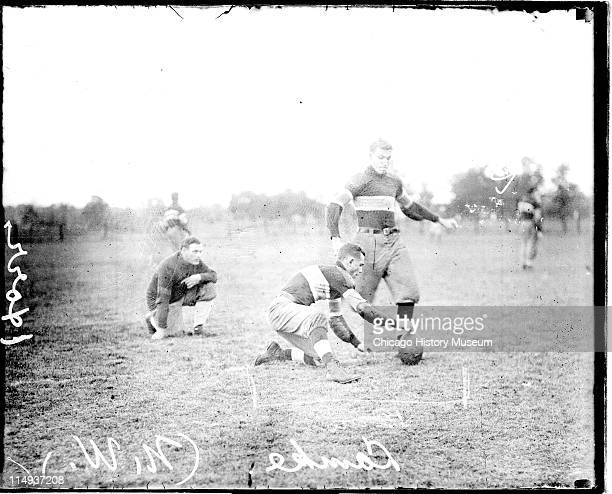 Informal fulllength portrait of Northwestern University football player Ward kicking a football standing on an athletic field in or near Evanston...