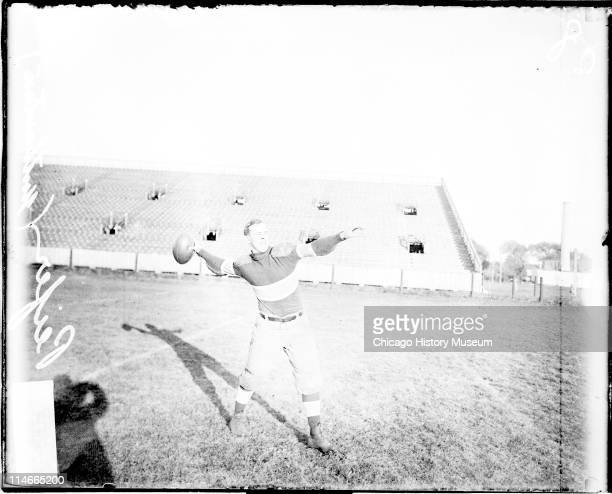 Informal fulllength portrait of Northwestern University football player Peifer cocking his arm to throw a football standing on an athletic field in...