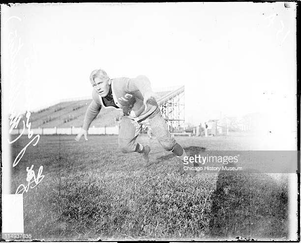 Informal full-length portrait of Northwestern University football player Jacobson lunging forward on an athletic field in or near Evanston, Illinois,...
