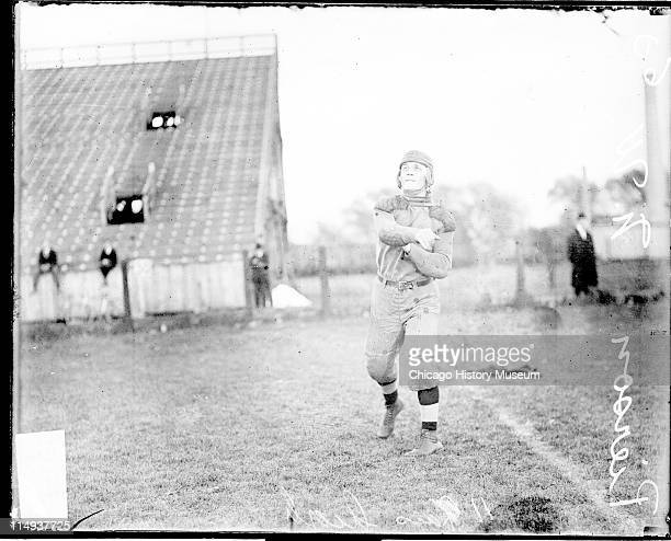 Informal full-length portrait of Northwestern University football player Pierson following through after throwing a football, standing on an athletic...
