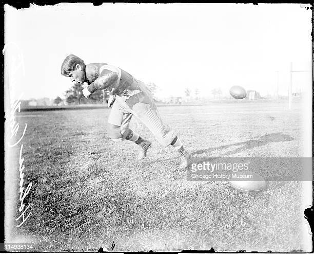 Informal fulllength portrait of Northwestern University football player Holmes running in profile on an athletic field in or near Evanston Illinois...