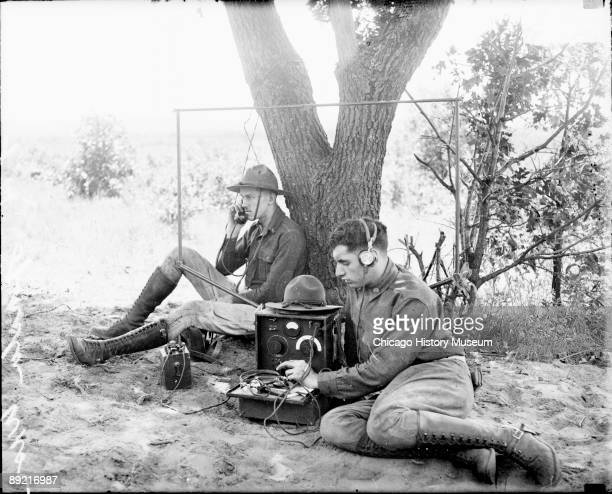 Informal fulllength portrait of two soldiers in the 122nd Field Artillery Regiment sitting outdoors next to a portable radio device at Camp McCoy in...