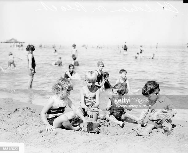 Informal fulllength portrait of two young girls and two young boys sitting and digging on the sand on the shore of a Lake Michigan beach in Chicago...