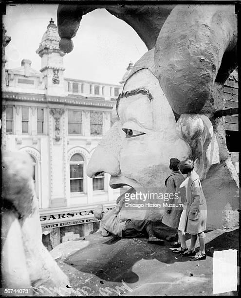 Informal fulllength portrait of two young girls standing on the shoulder of giant model of a court jester at the White City amusement park located at...
