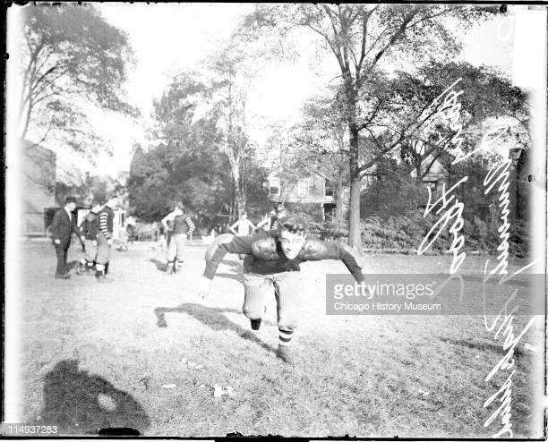 Informal fulllength portrait of University High School football player Albert Flood lunging towards the camera on a grass field in Chicago Illinois...