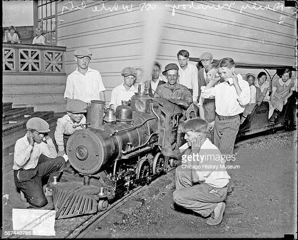 Informal group portrait of a group of Chicago Daily News boys kneeling and standing next to a miniature train ride at White City amusement park,...