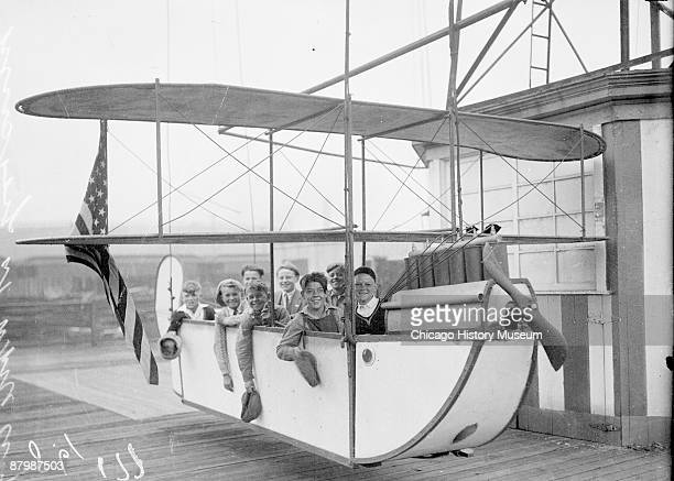 Informal group portrait of a group of Chicago Daily News boys and girls sitting in an airplane ride at White City amusement park located at 63rd...