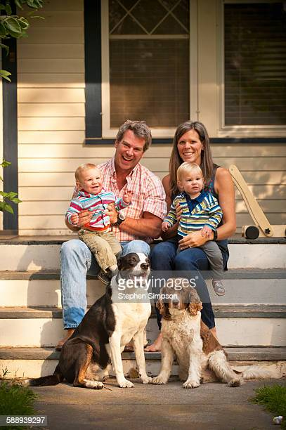 informal portrait of family of four [twins] - mom sits on sons lap stock pictures, royalty-free photos & images