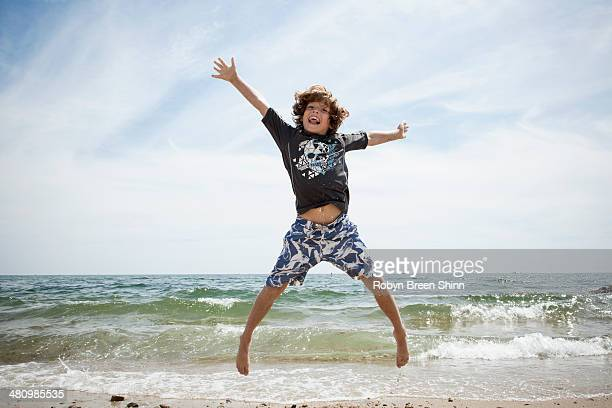 Informal portrait of jumping boy on beach at Falmouth, Massachusetts, USA