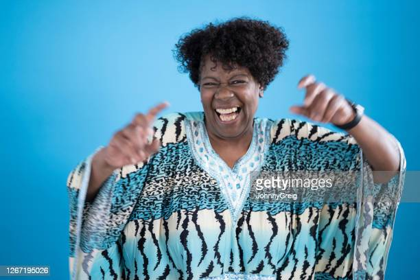 informal portrait of playful early 60s black woman in caftan - blue stock pictures, royalty-free photos & images