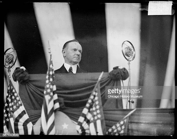 Informal portrait of President Calvin Coolidge standing behind a podium and looking to his left at a dedication ceremony for Wicker Park Lake County...