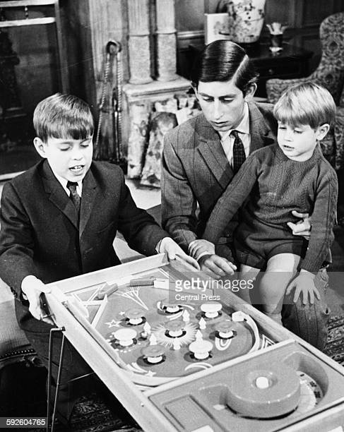 Informal portrait of Prince Charles playing a game of Bagatelle with his two young brothers Prince Andrew and Prince Edward at Sandringham April 1969