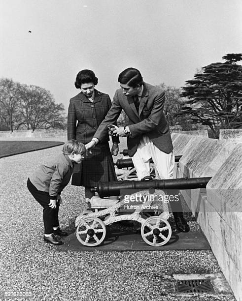 Informal portrait of Queen Elizabeth II and Prince Charles watching the young Prince Edward playing with a canon in the grounds of Windsor Castle...
