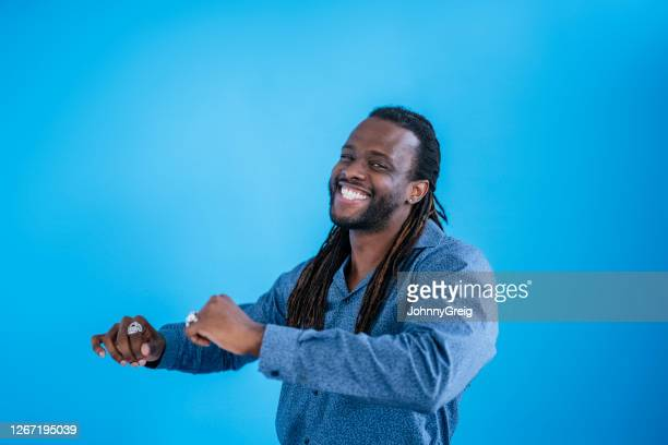 informal portrait of smiling early 30s black man dancing - two tone color stock pictures, royalty-free photos & images