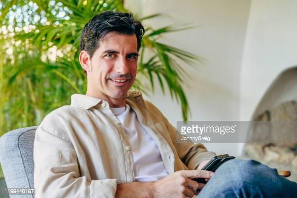 informeel portret van glimlachende volwassen spaanse man thuis - spaans en portugese etniciteit stockfoto's en -beelden