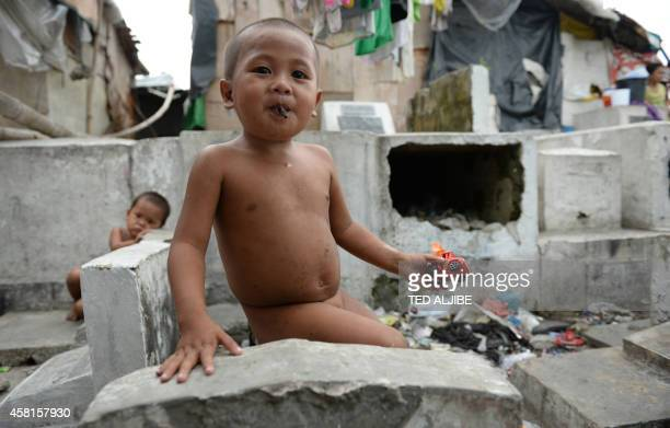 Informal settler children sit next to tombs at a cemetery in Manila on October 31 days ahead of the traditional All Souls' day Millions across the...