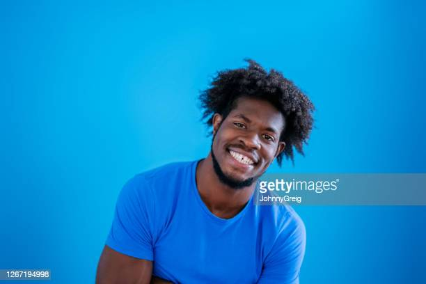 informal studio shot of early 20s black man in blue t-shirt - royal blue stock pictures, royalty-free photos & images