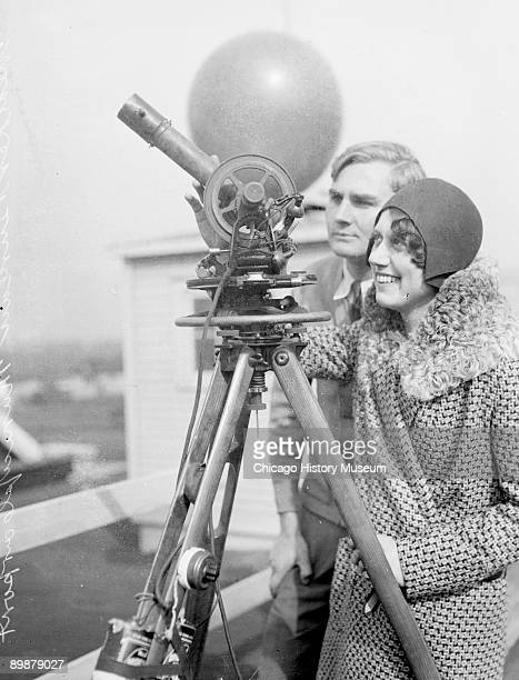 Informal threequarter length portrait of an unidentified woman standing behind a telescope sitting on a tripod on the roof of a building at Municipal...