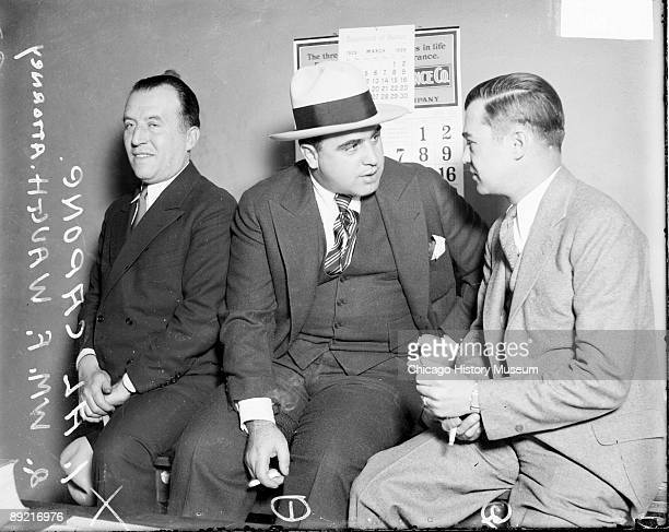Informal threequarter length portrait of attorney William F Waugh of the American Legion and gangster Al Capone talking sitting on a table in a room...
