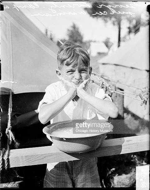 Informal threequarter length portrait of George Lorentz a boy squirting water out of his mouth standing behind a wooden railing at a Reserve Officers...