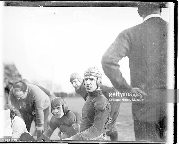 Informal three-quarter length portrait of Illinois University football player Baum looking at the camera, kneeling next to a group of teammates and...
