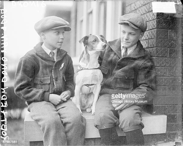 Informal threequarter length portrait of Robert and Edward Donovan sitting with a small dog on a wall in front of a building in Chicago Illinois 1928