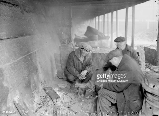 Informal threequarter length portrait of three hobos sitting under a covered structure in Chicago Illinois 1929 Debris is visible in the foreground...