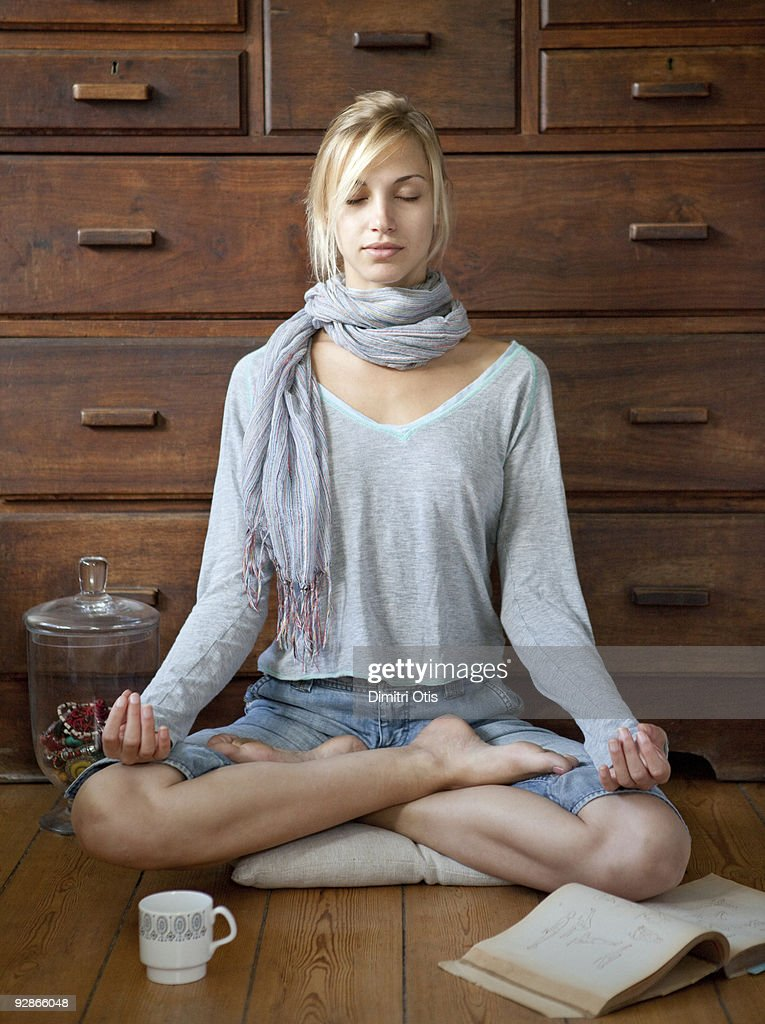 informal young woman doing yoga at home : Stock Photo