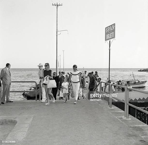Informality is the order of the day as Jacqueline Kennedy carrying a tote bag and holding Caroline by the hand walks up the pier at Amalfi known for...