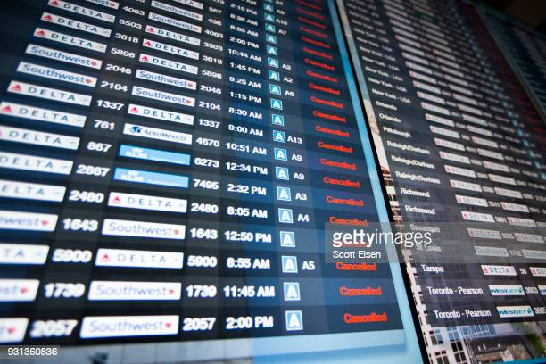Information boards at Logan International Airport show hundreds of cancelled flights as Winter Storm Skylar bears down on March 13 2018 in Boston...