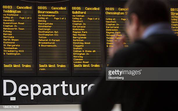 Information boards display cancelled train departures due to adverse weather conditions as commuters wait at Waterloo train station in London UK on...