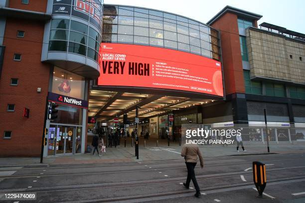 """Information on the local """"Very High"""" local Covid alert level is displayed on a large advertising space in central Manchester, north-west England on..."""