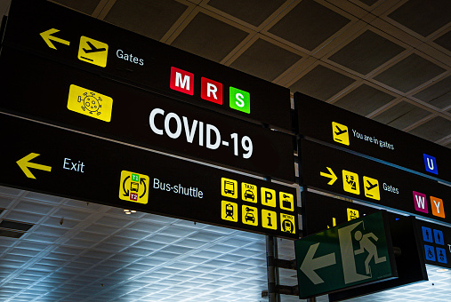 Information panel with Covid-19 word on it at an international airport. 1208828267