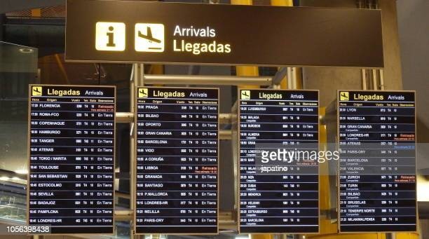 information screen of departures and arrivals at an airport - llegada fotografías e imágenes de stock