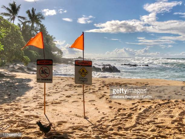 information sign on beach against sky - hawaii flag stock pictures, royalty-free photos & images