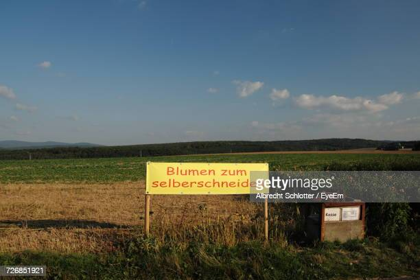 information sign on grassy field against sky - albrecht schlotter foto e immagini stock