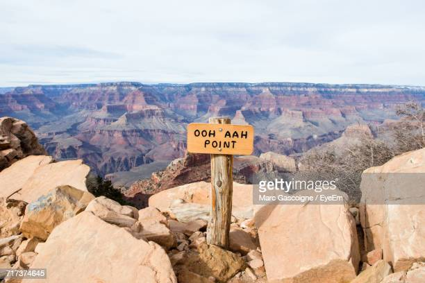 information sign on mountain against sky - grand canyon stock-fotos und bilder