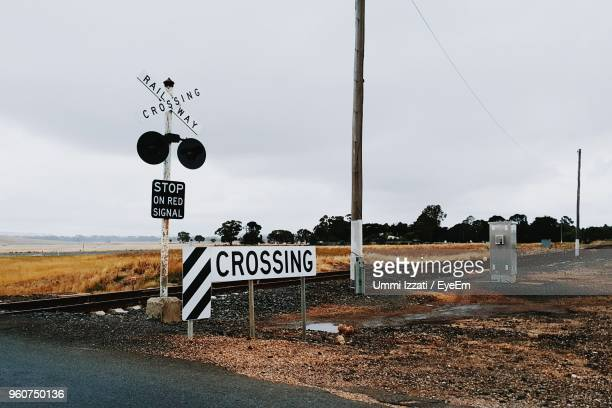 information sign on road against sky - railroad crossing stock pictures, royalty-free photos & images