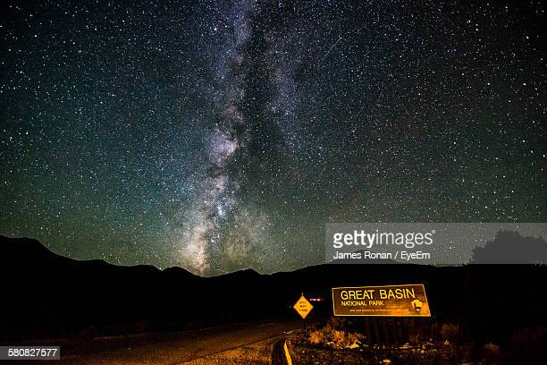 information sign on road by silhouette mountains against star field - great basin stock pictures, royalty-free photos & images