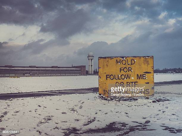 information sign on snow covered runway by tower at tempelhof airport during winter - tempelhof airport stock pictures, royalty-free photos & images
