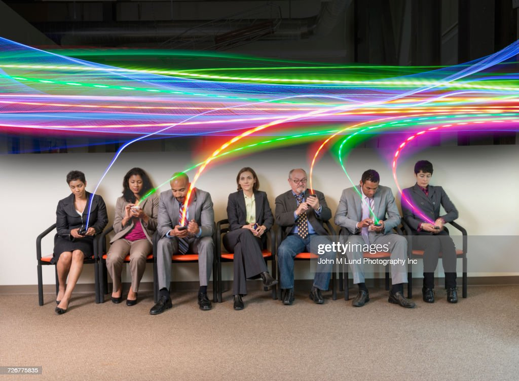 Information streaming to cell phones of business people sitting in a row : Stock Photo