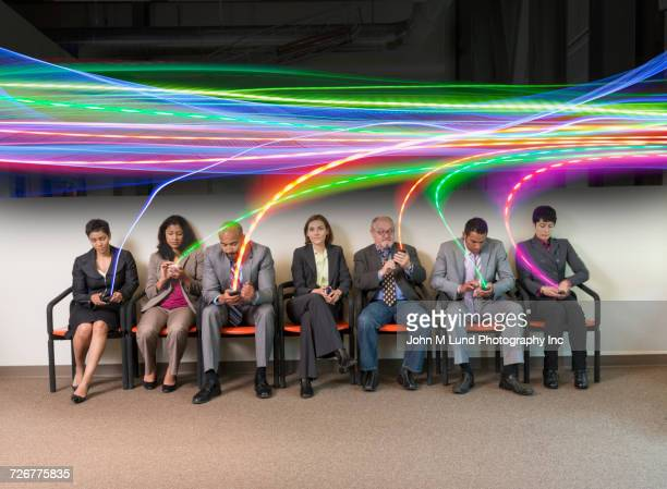information streaming to cell phones of business people sitting in a row - john lund stock pictures, royalty-free photos & images